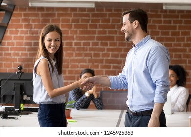Smiling team leader handshaking successful employee, congratulating with job promotion, business victory, thank,  encouraging, rewarding for good work, ceo shaking hand female office worker, respect