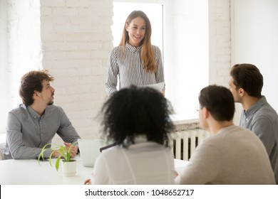 Smiling team leader or woman boss presenting new project or speaking about business results to employees at meeting, friendly advisor holding contract convincing investors or clients to make deal