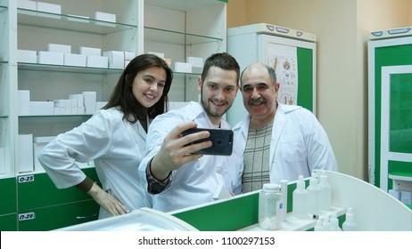 Smiling team of pharmacist taking selfie at hospital pharmacy