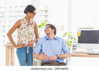 Smiling team using computer at desk in the office