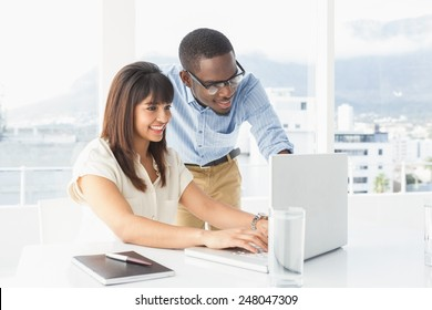 Smiling team using laptop together in the office