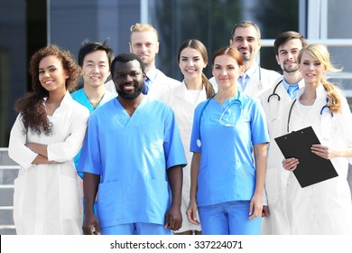 Smiling team of young doctors against hospital entrance
