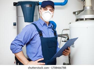 Smiling technician servicing an hot-water heater during coronavirus pandemic