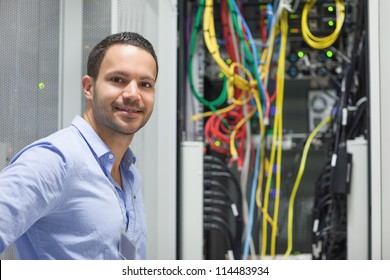 Smiling technician standing next to the data store