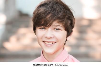 Smiling teen boy 14-16 year old having fun outdoors. Looking at camera. Teenagerhood. Positive mood.