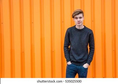 Smiling teen boy in black over contrasting orange background portrait with copyspace