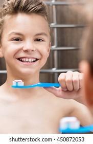 Smiling teen boy brushing teeth in bathroom