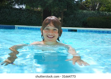 Smiling teen boy swimming in the pool surrounded with white flower bushes in the background.