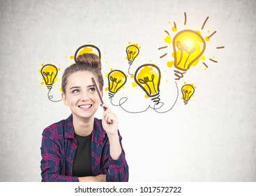 Smiling teen girl in a checkered shirt is sitting with a pencil near her forehead and thinking. She is looking up. A few yellow light bulbs drawn on a concrete wall