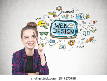 Smiling teen girl in a checkered shirt is sitting with a pencil near her forehead and thinking. She is looking up. A concrete wall with a web design sketch