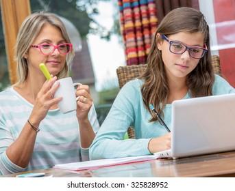 smiling teen girl doing homework with a blond teacher