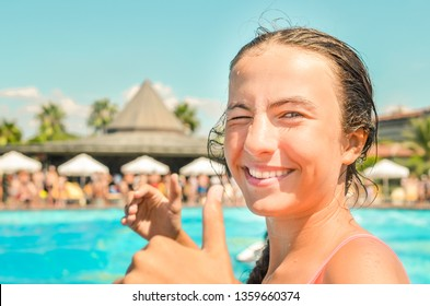 Smiling teen girl enjoing summer vacation at the hotel pool with palms and sun umbrellas on the background. Girl shows thumbs up symbol. Summer holidays, fun summertime and watersports concept.