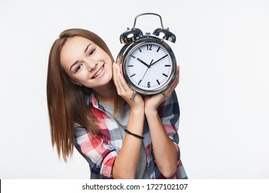 Smiling teen girl holding big clock, isolated portrait over white background. Time concept