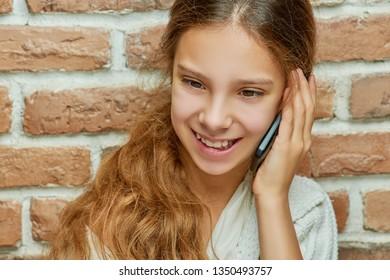 Smiling teen girl with long hair is talking on mobile phone against brick wall.