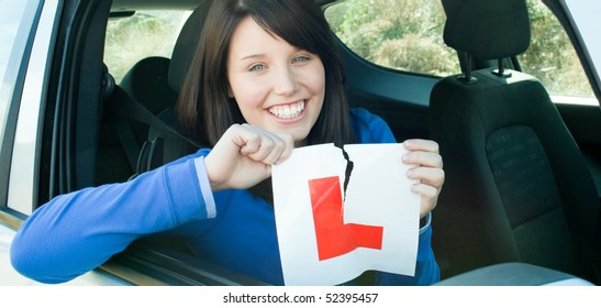 Smiling teen girl sitting in her car tearing a L-sign after having her driver's licence