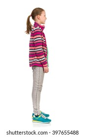 Smiling teen girl in striped fleece jacket, jeans and sneakers standing and looking away. Side view. Full length studio shot isolated on white.