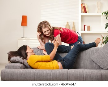 Smiling teen girls listening music together on earphones at home.