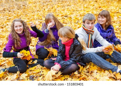 Smiling teen group sitting on yellow leaves