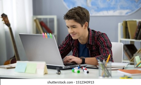Smiling teen male chatting with friends in social networks sitting front laptop