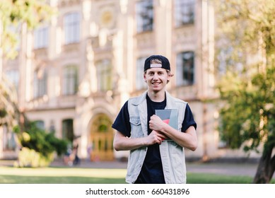 A smiling teen student with a notepad standing in a campus near his college. On the background of the caspouse. Student Life.