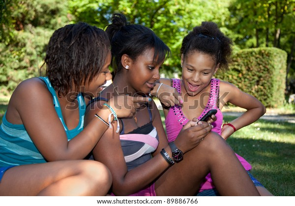 Smiling teenage black girls using a mobile phone at park