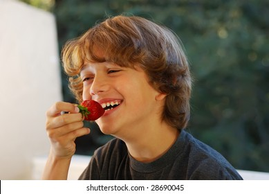 Smiling teenage boy about to bite a strawberry.