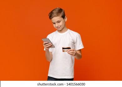 Smiling teenage boy holding credit card and smartphone in both hands, buying via internet, orange studio background