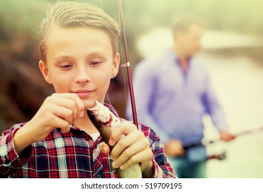 Smiling teenage boy releasing catch on hook fish outdoors