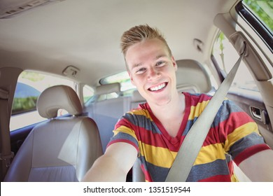 Smiling teenage boy sitting inside a car ready to drive