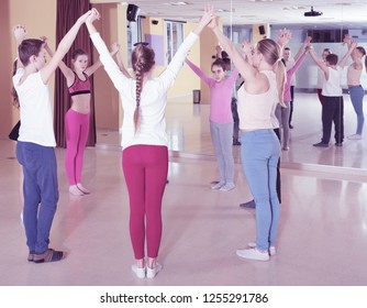 Smiling teenage boys and girls practicing circle dance with female trainer in dance hall