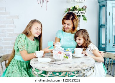 Smiling teenage daughter showing photos to mother and sister