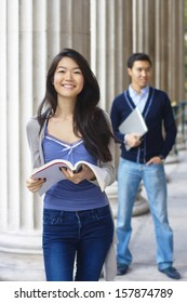 Smiling teenage female student outdoors with a boy at the background