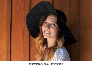 Smiling teenage girl with a black hat.