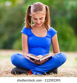 Smiling teenage girl in blue dress sitting in lotus position on green meadow in summer park and reading a book.