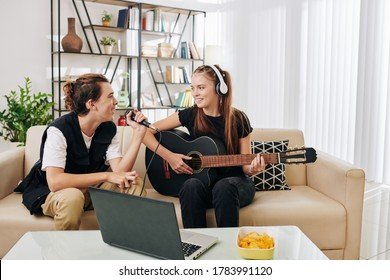 Smiling teenage girl in headphones playing guitar when her friend singing a song in microphone