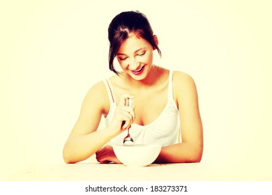 Smiling teenage girl holding spoon and eating from a bowl.