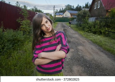 smiling teenage girl in a red striped shirt standing on the street between the houses, her arms crossed over his chest.