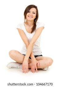 smiling teenage girl sitting on the floor with crossed legs, full length, white background