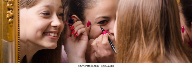 Smiling teenage girls putting make up in front of the mirror.