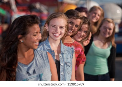 Smiling teenage girls standing behind each other in line