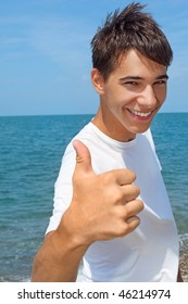 smiling teenager boy against sea shows ?? gesture