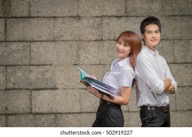 Smiling teenager Couple student in university uniform standing on wall background