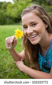 Smiling teenager holding a beautiful flower while lying on the grass in the countryside