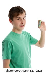 A smiling teenager holding some money cash rolled up in his hand.