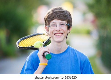 Smiling teenager holding a tennis racket in a suburban setting.