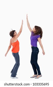 Smiling teenager keeping her hand in the air while her friend tries to touch it