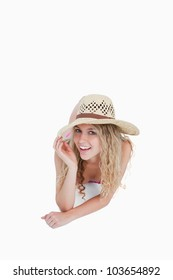Smiling teenager lying down while holding her hat brim against a white background