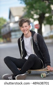 Smiling teenager on a suburban street sitting on his longboard and smiling cheerfully.