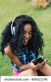 Smiling teenager portrait with headphones listening to music in a Park. South Beach Miami, Florida.