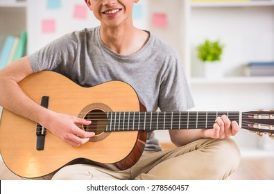 Smiling teenager sitting at home and playing guitar.